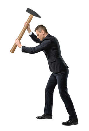 subjugation: Businessman standing side view to the camera in a suit raising a big mallet above his head in a conceptual image isolated on white Stock Photo