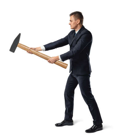 Side view of a businessman with big hammer in his arms destroying something, isolated on white background.