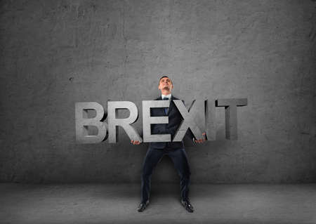 business skeptical: Businessman holding heavy 3d brexit word