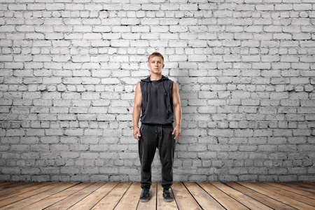muscled: Front view of muscled young man standing, on the background of white brick wall. Stock Photo