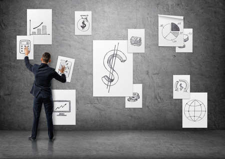 putting up: Businessman putting up business posters with sketches on concrete wall. Stock Photo