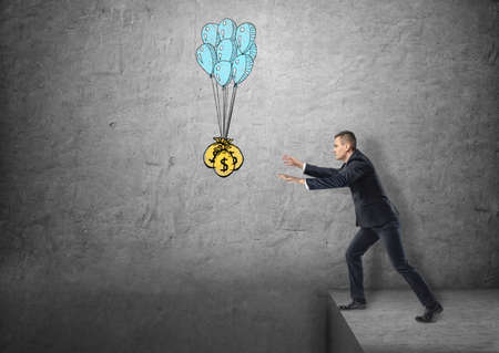 Businessman standing on the edge reaching for sacks of money hanged on balloons. Lust of money. Eagerness and zeal. Money-grubbing. Stock Photo