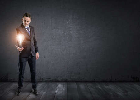 speculating: Front view of a businessman standing and holding glowing light bulb in his hand. Concepts and ideas. Business staff. Speculating and analyzing. Brainstorming.