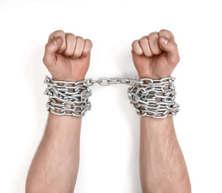 fetter: Close up view of chained mans hands. Fetter and captivity. Lack of freedom.
