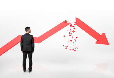 Back view of a businessman looking at red broken arrow of falling graph isolated on white background. Stock market selloff. Economic crisis. Bad luck and problems. Archivio Fotografico