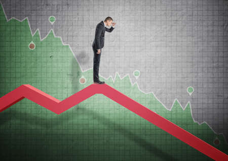 selloff: Businessman standing on falling diagram and peering into the future on the background of stock market selloff. Economic crisis. Bankruptcy and money devaluation.