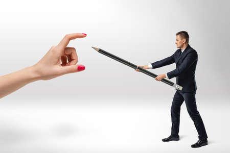 dominacion: El hombre de negocios defenderse de mano grande de la mujer con el lápiz grande en sus brazos. Jefe y subordinado. De pie contra la dominación. La desobediencia e insubordinación. Foto de archivo