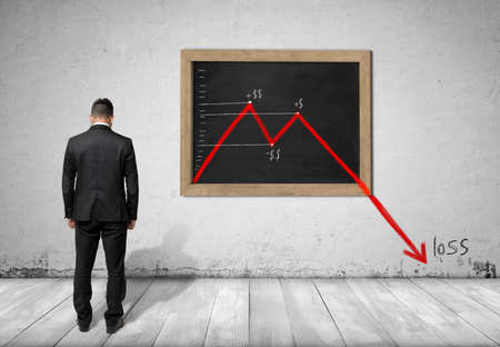 Back view of a businessman standing in front of blackboard with falling diagram that goes down to the floor with loss word near it. Financial and economic crisis. Stock market falling.
