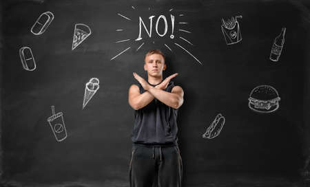 renounce: Muscled young man showing stop sign with his hands and says no to unhealthy food on the background of blackboard. Healthy lifestyle. Sportive nourishment.