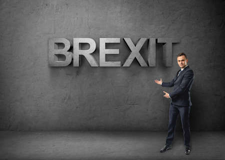 withdrawal: Businessman stands showing big 3d brexit word by both hands on concrete background. British withdrawal. Euroscepticism. Unired Kingdom and European Union.