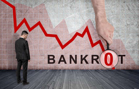 selloff: Back view of a businessman standing on the background of falling diagram with big mans hand with a magnifier and bankrot inscription. Stock market selloff. Financial and economic crisis.