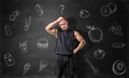 Muscled young man pondering on what to choose: junk or healthy food on the background of blackboard. Fitness and sport. Nutrition and nourishment.