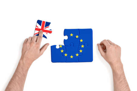 withdrawal: Hand holding piece of jigsaw puzzle with flag of European Union and Great Britain isolated on white background. Brexit puzzle concept. British withdrawal. Significant decision. Stock Photo