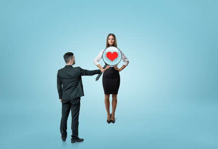Businessman looking through womans chest with a magnifier and seeing a heart inside. Business staff. Relationsip at work. Employment issues.