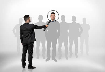 Back view of a businessman looking through magnifying glass on the head of the man that is surrounded by grey silhouettes. Hiring and giving a job. Employment and occupation. Stock Photo