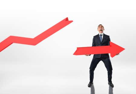 白い背景に分離された両手で大きな壊れた矢印を保持している実業家。不況と衰退。株式市場が急落。闘争と努力。
