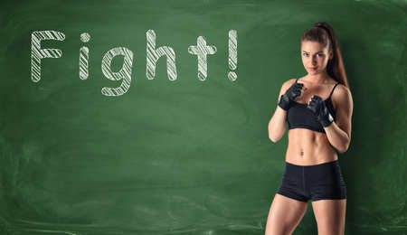 Cropped portrait of fitness girl clenching her fists ready to fight on the background of a chalkboard. Workout and fitness. Strong woman. Active lifestyle.