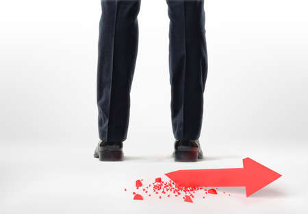 broken back: Back view of cropped legs and feet of a businessman with red broken arrow behind him isolated on white background. Stock market. Economic and financial crisis.
