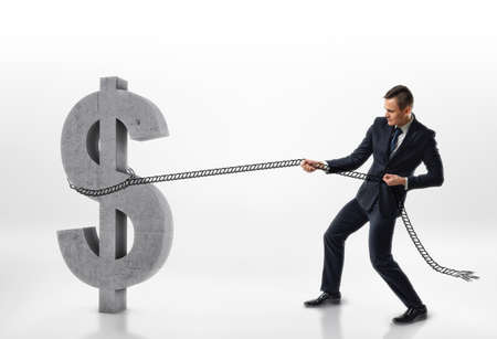 Businessman pulling big concrete 3d dollar sign with a rope isolated on white background. Making money. Success and profit. Hard work. Stock Photo