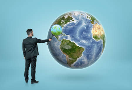 optical people person planet: Back view of a businessman looking through magnifying glass on the Earth and seeing grass and green plant. Eco-friendly living. Environment and ecology.