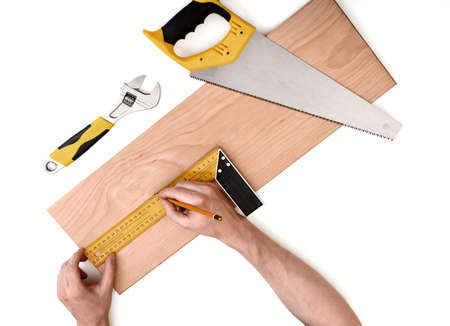 Close up view of a mans hands measuring wooden plank with iron ruler with angle bar with adjustable wrench and a handsaw near it isolated on white background. Tools and instruments. Stock Photo