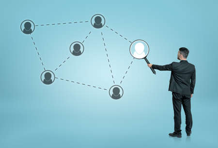 Back view of a businessman enlarging one of the social network icons connected by dotted lines with a magnifier. Searching and investigation. Employment issues. Global communication. Stock Photo