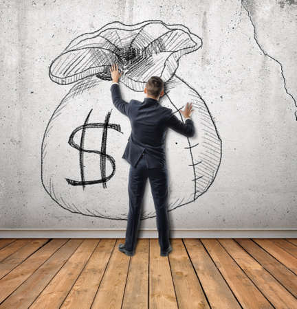 Back view of businessman touches a sketch of money bag on concrete wall. Setting and achieving goals. Desire and dream. The obsession with the money. Stock Photo