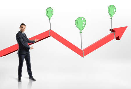 attaining: Businessman presents growing red arrow with air balloons. Targeting success and happiness. Success and development. Prosperous business.