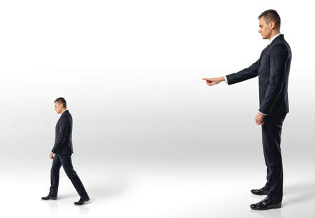 reproach: Businessman points at another man following in the direction indicated. Reproach and remark. Superiors and subordinates. Losing a job.