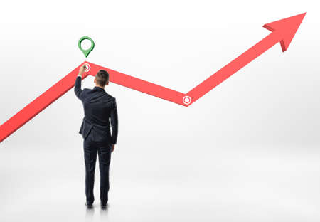 Back view of a businessman making a mark on rising diagram isolated on white background. Stock market. Rise of shares. Profit and success.