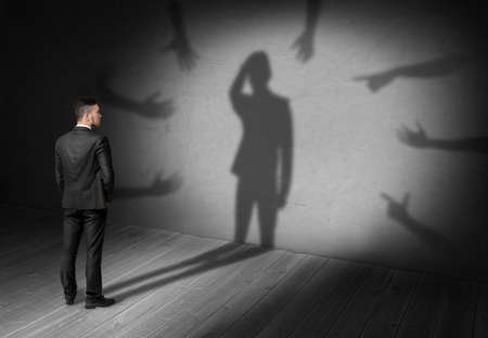 quandary: Businessman looking at his shadow where many hands reach for him forcing grab his head. Difficulties at work. Problems and issues. Predicament. Stock Photo