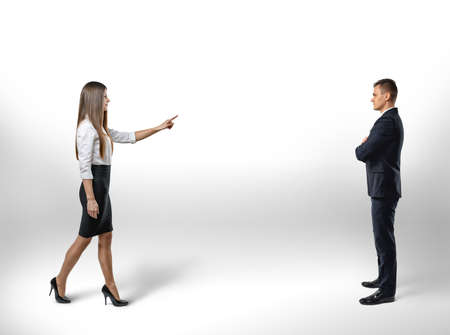 first move: Businesswoman pointing a finger takes a step toward to businessman. Make the first move. Select. The relationship between colleagues. Stock Photo