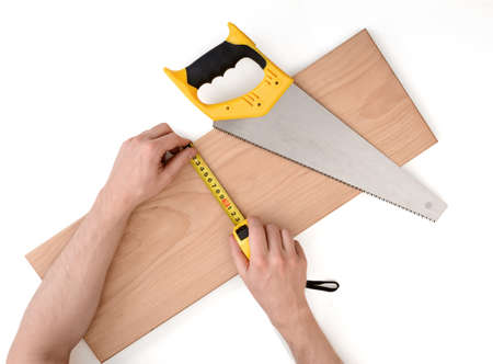 Close up view of a mans hands measuring wooden plank with tape line, isolated on white background. Tools and instruments.