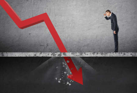 depreciation: Businessman looking down at the falling red arrow destroying a concrete barrier. Collapse and drop. Fall and depreciation. Regression and deterioration. Crisis.