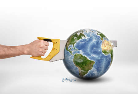 Mans hand sawing a globe with a saw. Destruction of the planet. Anthropogenic impacts. Environmental effects. Harm and damage. Elements of this image are furnished by NASA.
