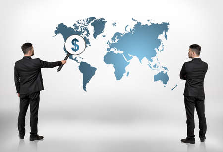 Back view of two businessmen looking at world map with big magnifier enlarging dollar sign on North America. World economy. The capital of the world economy. Profitable investment. Financing market.