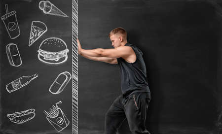 rejection: Athletic man pushing the drawn wall with fast food sketches. Rejection of unhealthy lifestyle. Choosing the proper nutrition. Well-being. Stock Photo
