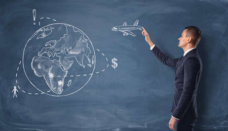 humanitarian: Businessman touching the drawn plane on the chalkboard with a globe. Recreation and tourism. Investing human and financial resources. Humanitarian assistance.