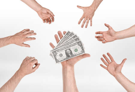 obtaining: Someone hand holding several dollar bills and other people hands trying to reach for them. Grabbing a chance. Obtaining business financing. Getting a loan.