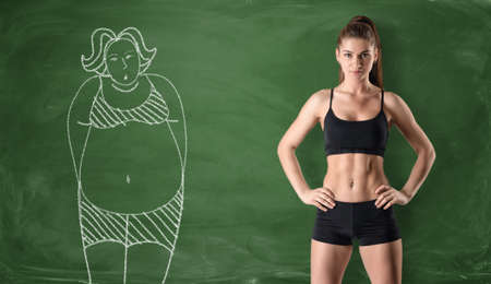 Sporty girl with a slim body standing at the right side and a picture of a fat woman drawn at the left side on a green chalkboard background. Getting rid of a pot belly. Losing weight. Before and after. Archivio Fotografico