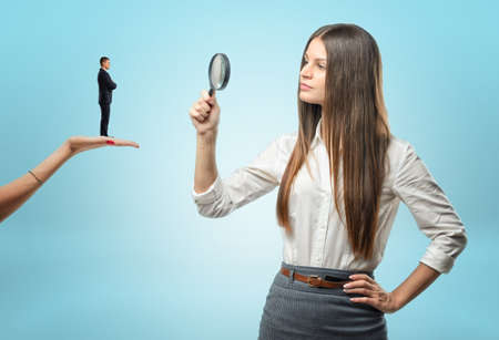 looking for job: Young woman looking at a tiny man with a magnifying glass while he is standing on another woman hand. Looking for an employee. Applying for a job. Considering candidates for posts. Stock Photo