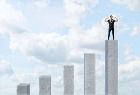 Five cement column with varied length and a businessman standing on the highest of them and showing his muscular arms. Being on the top. Leadership and dominance. Getting ahead of the competition.