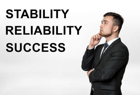 firmness: Cropped portrait of a businessman thinking with stability, reliability, success words beside him. Professional motto. Durability, strength, firmness. Ideas and concepts. Stock Photo