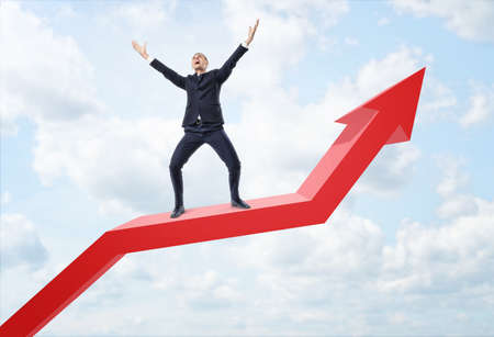 upturned: Businessman expressing happy and standing on a big red line graph with an upturned arrow on a background of the sky. Achieving success. Personal development and career progress. Growth of income.