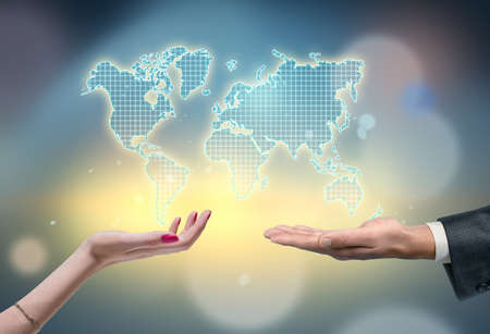 Two hands stretched out, male and female, with the outline of continents above them on the blurred background. Global issues. International trade and relations. Ecology and world peace.