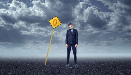 ineffective: An upset businessman standing on a rocky ground in front of a yellow road sign with a zero painted on it and there are dark clouds above him. Unachieved goals. Ineffective work. Emotional pressure.