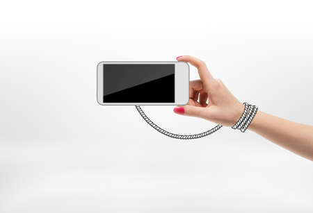 cell phone addiction: Woman holding mobile phone with drawn rope wrapped around her hand on white background. Modern technologies. Cell phone addiction. Electronic means of communication. Stock Photo