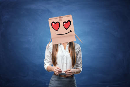 romance: Young beautiful businesswoman with cardboard box on her head with drawn smiley face with hearts instead of eyes. Anonymous person. Falling in love. Office romance. Love customers.