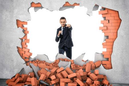 desarrollo económico: Un hombre de negocios de pie cerca del agujero en la pared que se acaba de hacer con un golpe duro, una pila de ladrillos rojos yacen debajo. Superando obstáculos. Aspectos de negocios. Desarrollo economico. Foto de archivo
