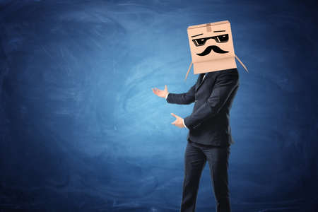 A businessman showing at something on the blue blackboard behind him, he is wearing a cardboard box with drawn sun glasses and moustache on his head. New opportunities. Interesting proposals. Confidence and professionalism. Anonymous person.